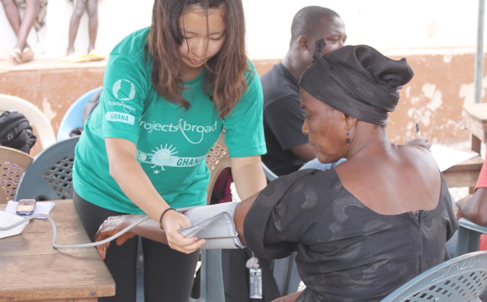 地域型ヘルスチェックでガーナ人女性の血圧測定を行う公衆衛生インターン